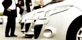 Flota de vehículos junto a la imagen difuminada de varios ejecutivos.ºFlota de vehículos junto a la imagen difuminada de varios ejecutivos.