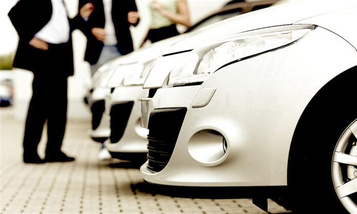 Flota de vehículos de renting junto a la imagen difuminada de varios ejecutivos. // FOTOGRAFÍA: FLEET PEOPLE