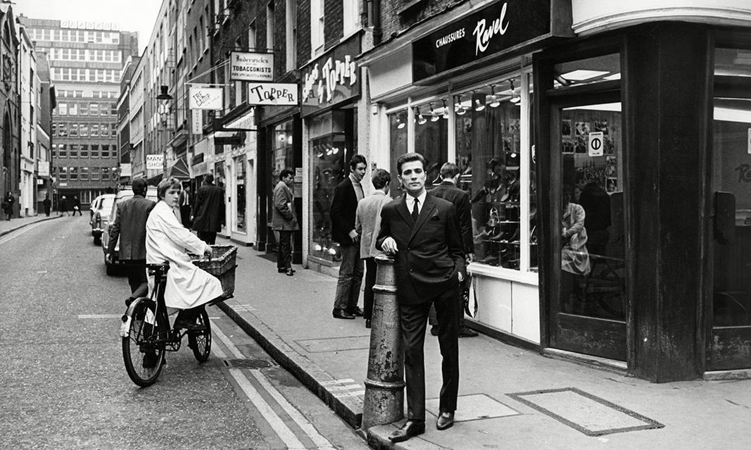 John Stephen, posando en febrero de 1966 en Carnaby Street. El 75% de las tiendas que se ven detrás de su espalda le pertenecían en esa época, la de su máximo esplendor empresarial y textil. // FOTOGRAFÍA: BEVERLEY GOODWAY / ANL / REX