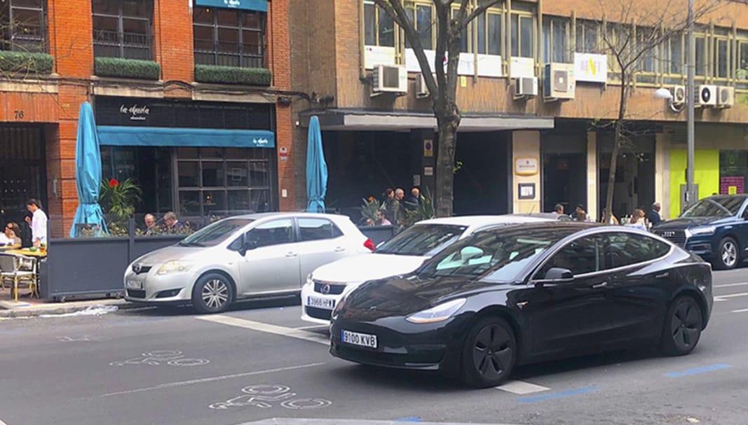 En primer término, un Tesla Model 3 eléctrico de color negro, circulando por una céntrica calle de Madrid. // FOTOGRAFÍA: FLEET PEOPLE