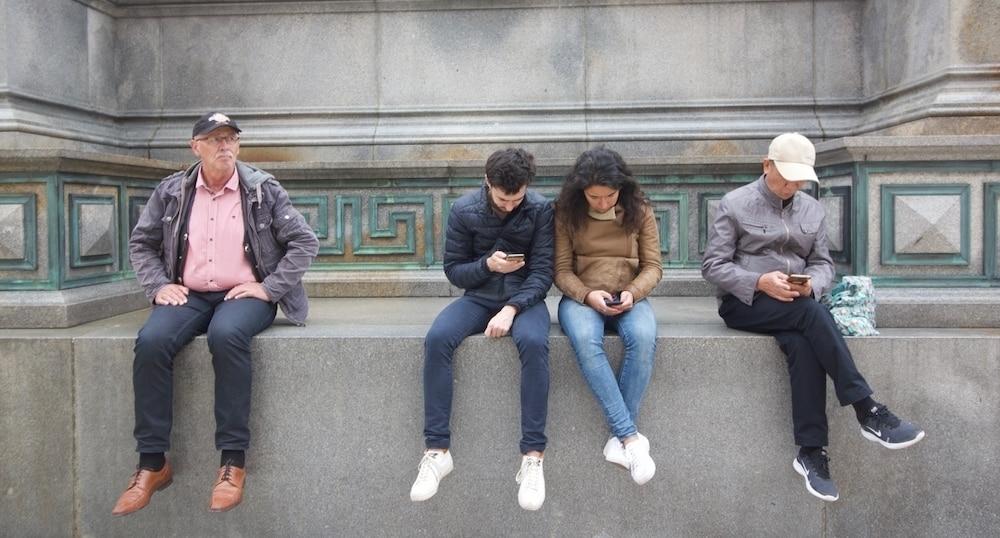 Un grupo de personas leen el móvil en Viena (Austria). / CRHISTOPHER BURGUESS