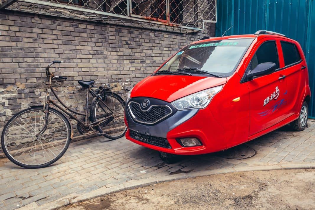 Un three-wheeler descansa junto a una bicicleta en una calle de Pekín, en 2019. Los vehículos pequeños pueden ser una clave para este mercado. / SHUTTERSTOCK