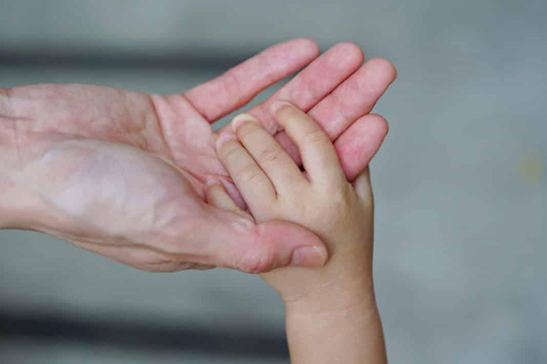 mano de adulto coge la de un bebé. Boontoom Sae-Kor
