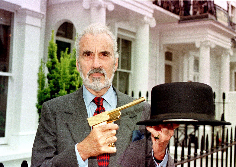 El siempre elegante y gran actor Christopher Lee, quien aparte de ejercer como Drácula interpretó con maestría al villano Scaramanga en 'El hombre de la pistola de oro' (1974). En la imagen, Lee posa en Londres en julio de 1998 junto con la mítica pistola de oro del filme y otro icono de la saga Bond, el sombrero con cuchila incorporada (varias décadas antes de 'Peaky Blinders') que usó Oddjob en '007 contra Goldfinger' (1964). // MICHAEL STEPHENS