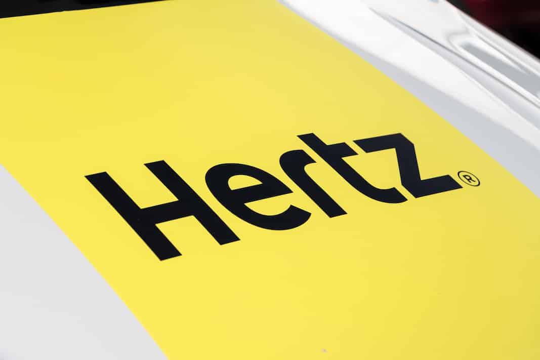 El logo de la alquiladora de vehículos Hertz y Avis, en el capó de una furgoneta, en Madrid. Fotografía de Manuel Esteban